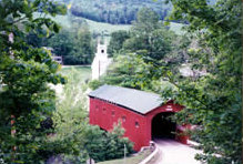 Covered bridge near homes and chruch in Vermont